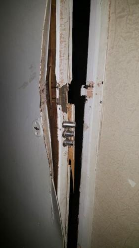 Искареженное полотно металлической двери после вскрытия МЧС