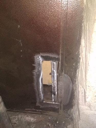 Вырезанная старая петля на металлической двери стоматологии