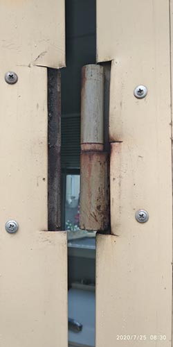 Старая металлическая петля на двери проходной